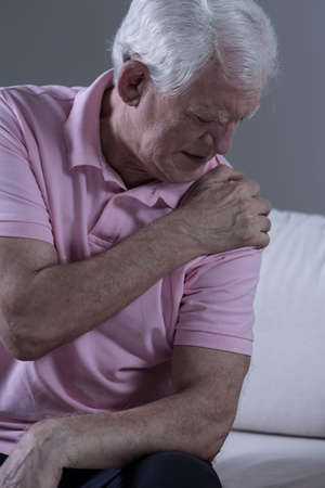 shoulder problem: Senior sad man with acute pain in his shoulder joint Stock Photo