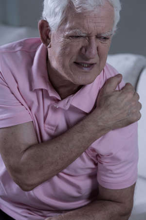 shoulder problem: Aged sad grandfather with painful shoulder joint Stock Photo
