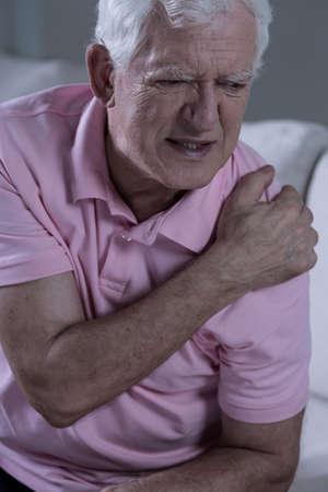 epaule douleur: Grand-p�re triste vieilli avec articulation de l'�paule douloureuse Banque d'images