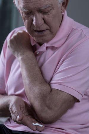 Senior man lubricating with analgetic cream his elbow photo
