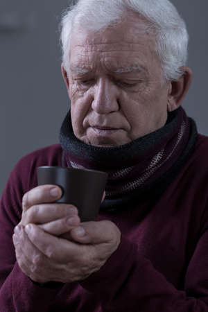 seniors suffering painful illness: Close-up of aged sick man with sore throat drinking tea