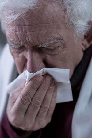 Elderly sick man blowing his rainy nose Stock Photo