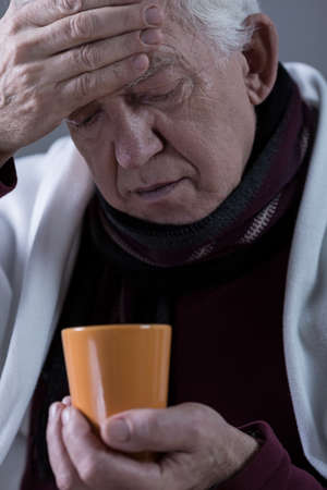 Senior sick man with high temperature drinking hot tea
