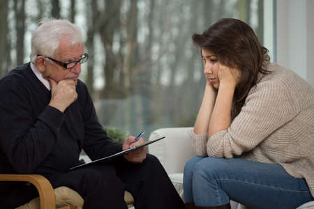diagnosing: Older experienced psychologist diagnosing young troubled woman Stock Photo