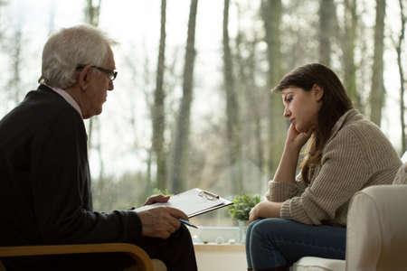 심리학자의 사무실에 앉아 젊은 매력적인 슬픈 여자