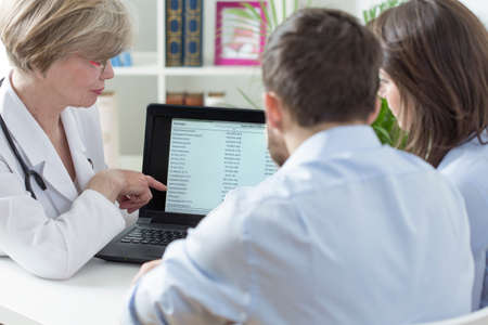 gynecologist: Female gynecologist analyzing with couple tests results Stock Photo