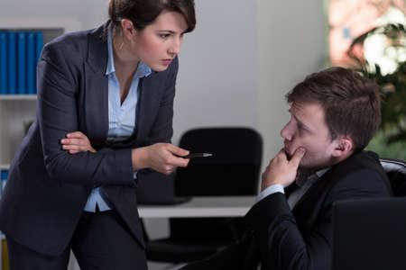 threatening: Boss threatening her male employee, horizontal