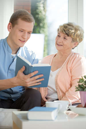 social work aged care: Picture of male caregiver assisting senior woman Stock Photo