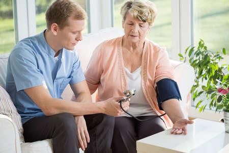 hipertension: Hombre que trabaja como enfermera toma la presión arterial