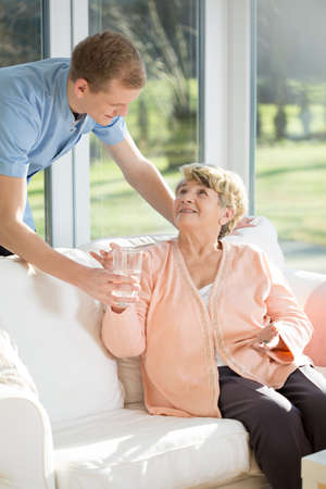 social work aged care: Male care assistant caring about elder woman