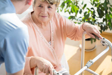 pensioner: Horizontal view of nurse assisting disabled pensioner