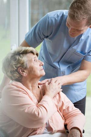 Male nurse caring about ill senior woman