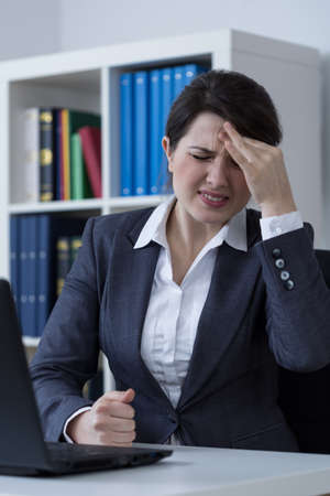 sedentary: Female office worker having migraine at work