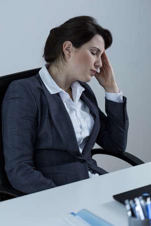 sedentario: Imagen de la empresaria con exceso de trabajo sentado en el escritorio Foto de archivo