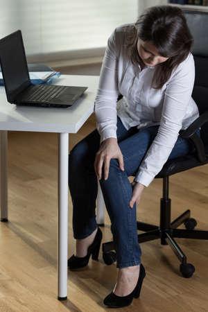 sedentario: Empresaria que tiene la pierna hinchazón causada por el trabajo sedentario Foto de archivo