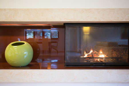 Close-up of lighted fireplace in new big room