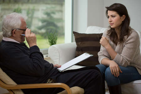 anxiety: Young woman talking with her older psychologist Stock Photo