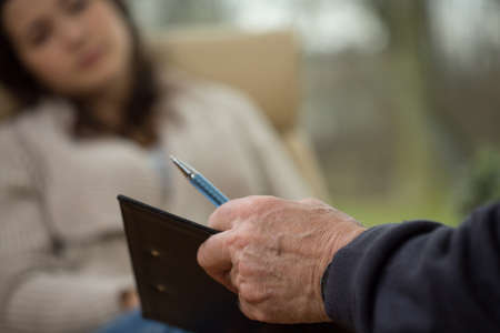 patient's history: Close-up of psychologist writing down patients history Stock Photo
