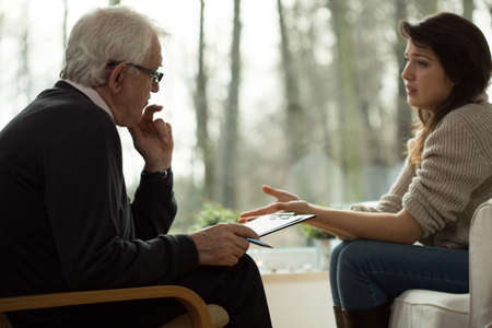 mental disorder: Young woman lamenting to her elderly psychologist Stock Photo
