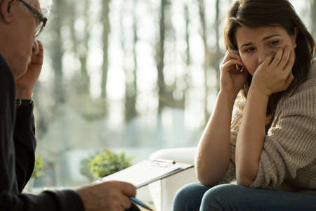 psychotherapy: Young depressed woman taking advice from her psychologist
