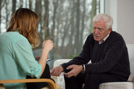 advising: Young female psychologist advising to older man