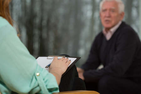 medical cabinet: Close-up of psychologist writing aged mans symptoms
