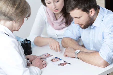 Couple choosing characteristic of their future child from in vitro photo