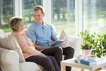 Male carer spending time with elder woman Stock Photo