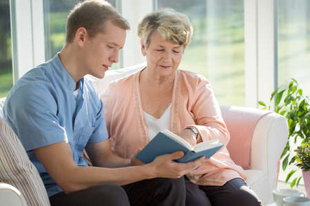 carer: Male senior care assistant caring about elderly woman