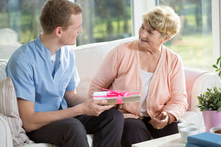 acknowledgment: Senior woman giving gift her male nurse Stock Photo