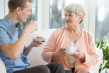 care worker: Elder woman and male nurse drinking coffee Stock Photo
