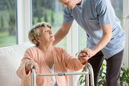 ancianos caminando: Mujer lisiada utilizando andador asistido por el fisioterapeuta