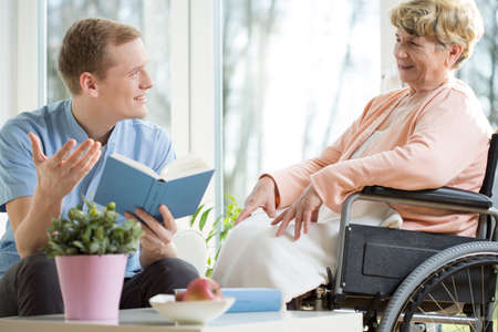 persona en silla de ruedas: Hombre asistente de cuidado de leer el libro mujer mayor