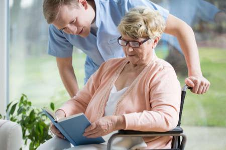 enfermeria: Retrato de la mujer mayor con discapacidad libro de lectura Foto de archivo