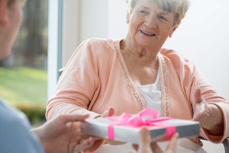giving: Old woman giving present her care assistant Stock Photo