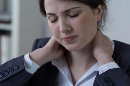 Vrouwelijke witte-boorden-werknemer met pijn in de nek