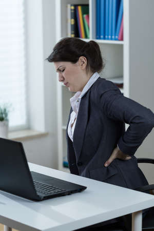 dolor de espalda: Oficinista que tiene dolor de espalda causado por el trabajo sedentario Foto de archivo