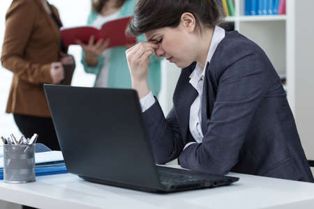 Female clerk having sinus pain at work photo