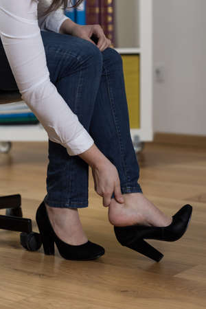 business woman legs: Painful feet after day in high-heeled shoes Stock Photo