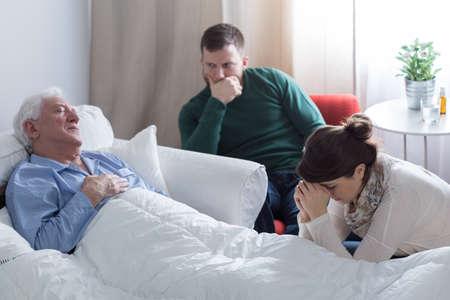 ベッドと彼の despaired の子供に横たわって瀕死の男