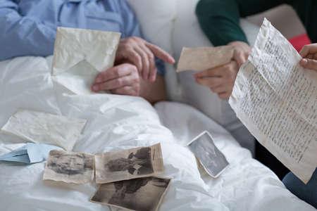 enfermo: Acostado en la cama y mirando fotos antiguas Foto de archivo