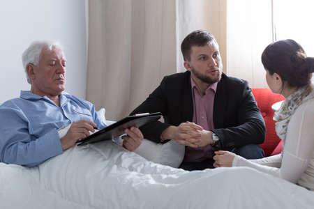 Afbeelding van terminaal zieke vader het maken van een testament Stockfoto