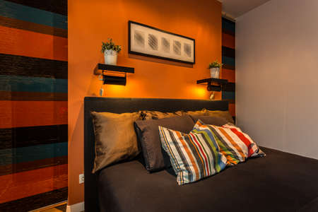 comfy: Comfy brown bed with striped pillows and walls Stock Photo