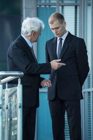 patron: Jefe mayor que habla con el joven empleado de oficina, vertical Foto de archivo