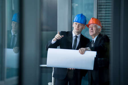 old building: Young engineer talking with senior boss, horizontal