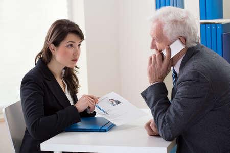 jefe: Protuberancia que habla en el teléfono durante la entrevista de trabajo Foto de archivo
