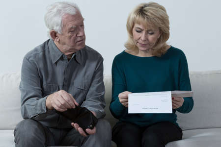 Aged couple sitting on the sofa and analyzing unpaid bills photo