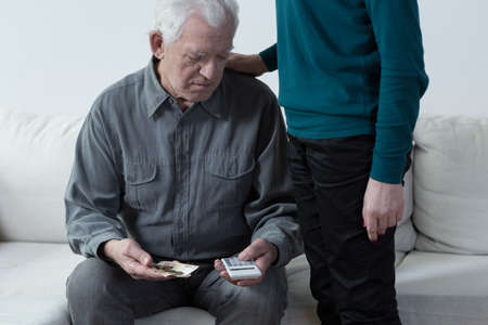 Poor senior man using calculator and counting money Stock Photo
