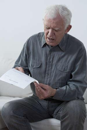 unpaid: Portrait of aged man reading unpaid bill