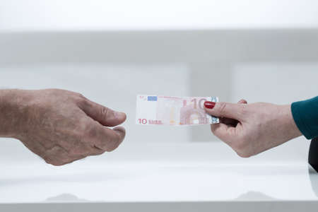 lend a hand: Close-up of female hand giving ten euro Stock Photo
